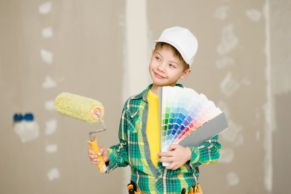 Boy with color samples and paint roller chooses the color of the walls of his room.